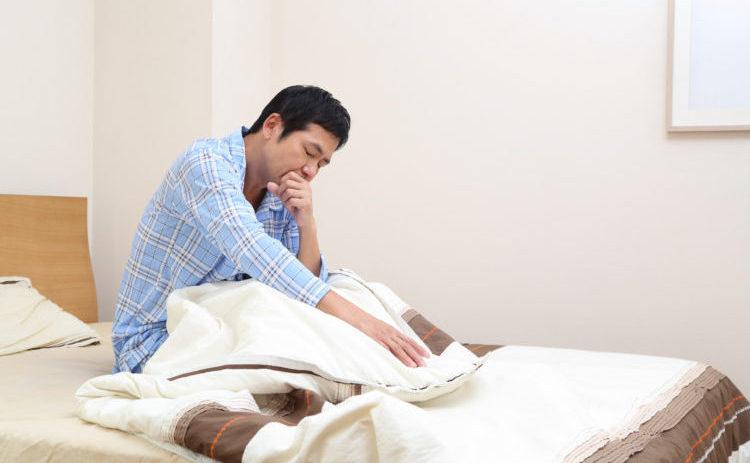 ベッドで咳き込む男性