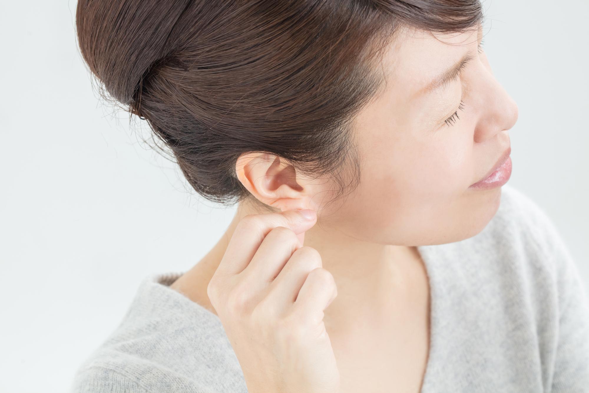 耳を引っ張る女性